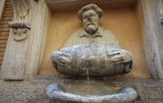 Statue of an old man pouring water from a barrel used as a fountain nicknamed 'The Porter'.